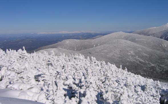 View of Kinsman Ridge and Cannon Mountain with the snow-covered Presidentials on the horizon (photo by Mark Malnati)