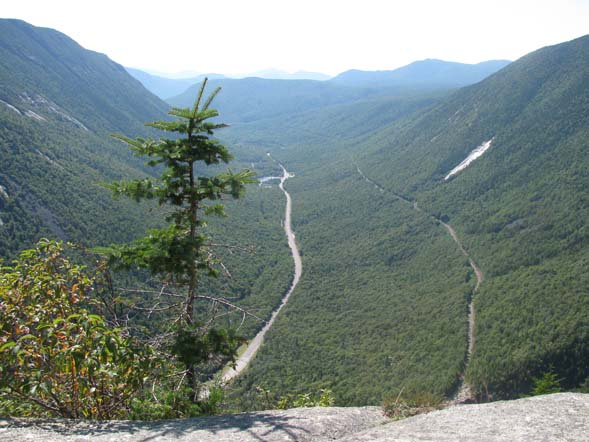 The view from Mount Willard's ledges showing the U-shape of Crawford Notch.  That's Route 302 running through the center and the railroad tracks are to the right of the road. (photo by Karl Searl)